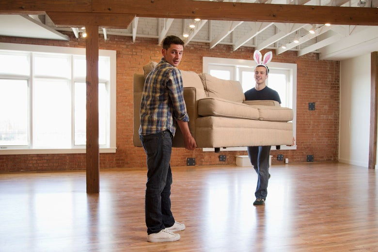 Two people moving a couch, but one has been illustrated to wear bunny ears.