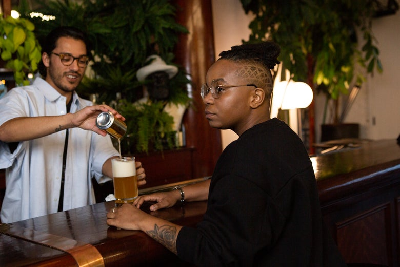 A transmasculine person getting a beer at a bar.