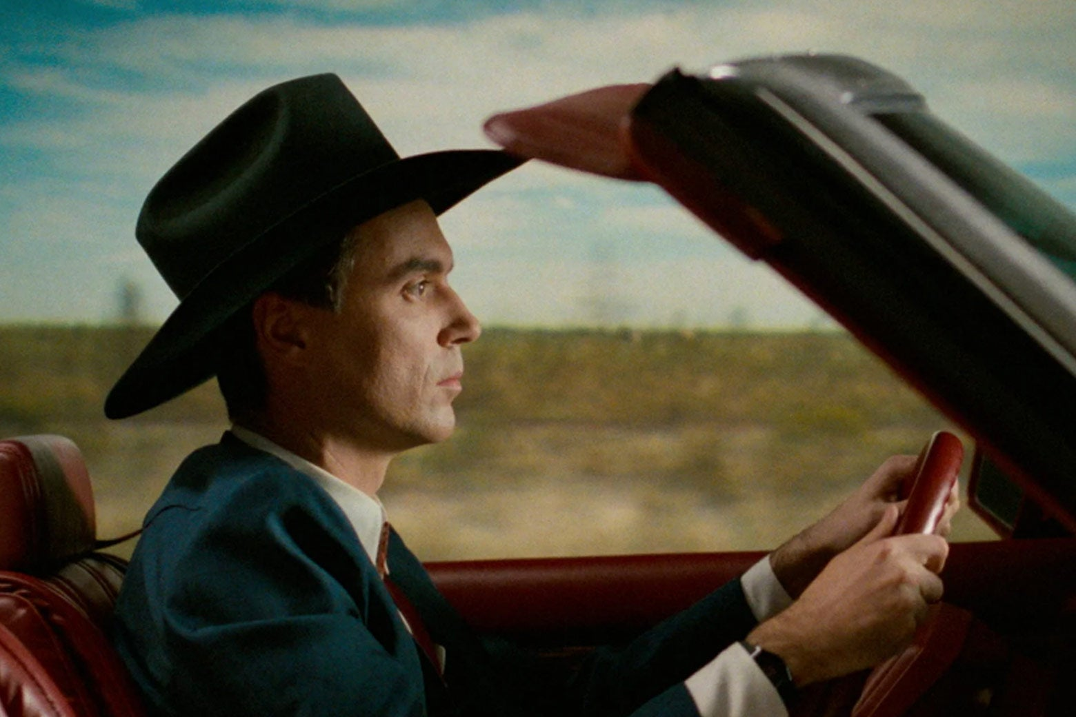 David Byrne driving in a convertible.