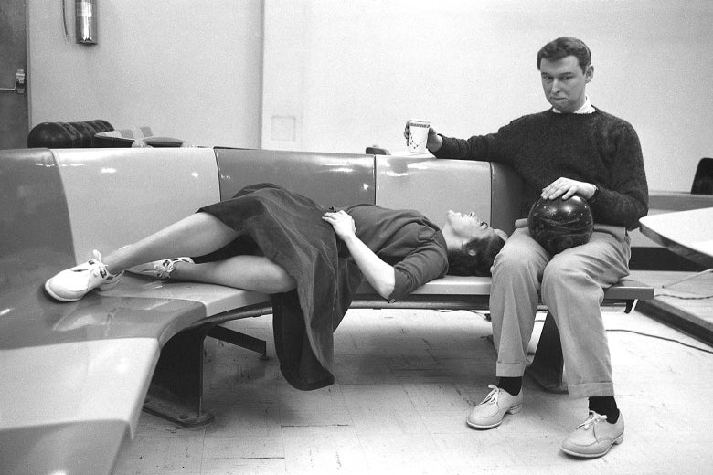 In a black-and-white photo at a bowling alley, May reclines on a bench next to Nichols, seated with a bowling ball in his lap and a paper coffee cup in his hand.
