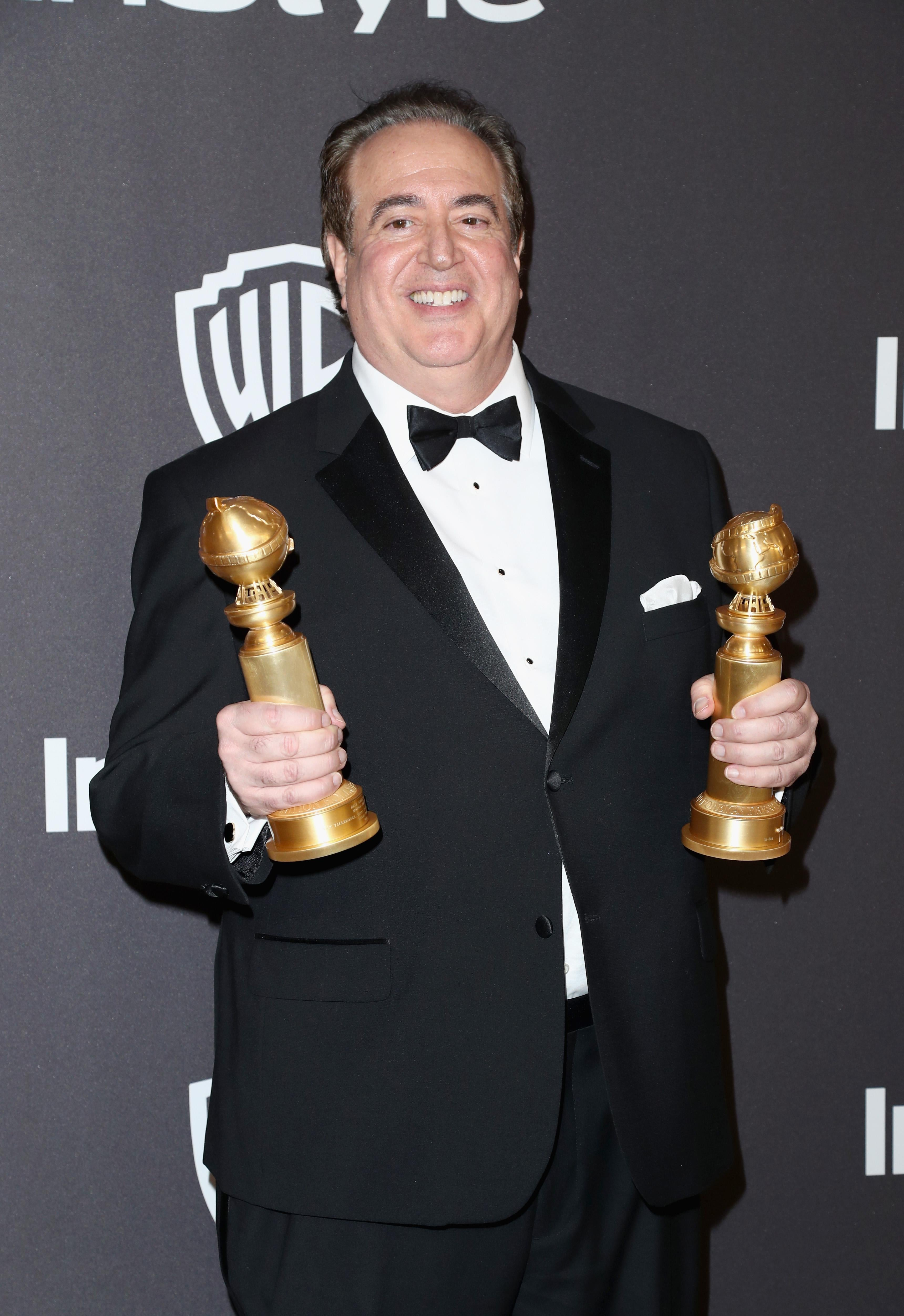 Nick Vallelonga holding his Golden Globes.