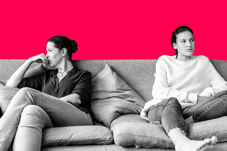 A mother and daughter sitting far apart on a couch, looking in opposite directions, upset.