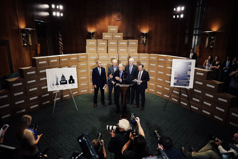 "Republican members of the Senate Judiciary Committee stand in front of a wall of empty boxes labeled ""Kavanaugh Files."""