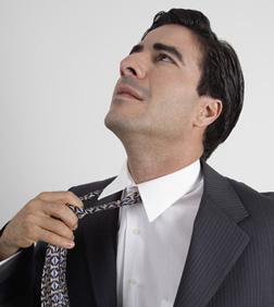 Portrait of a man adjusting his tie.