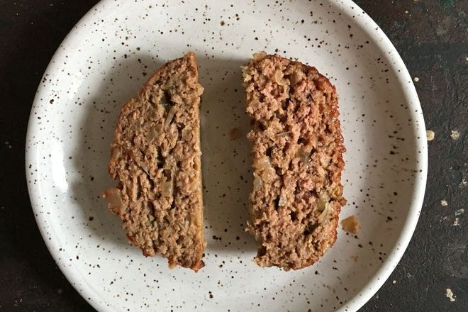 Two slices of meatloaf. The one on the left is more compact than the one on the right.