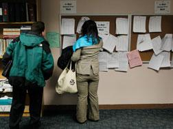 Unemployed people look over job listings on a board at a New York State Department of Labor Employment Services. Click image to expand.