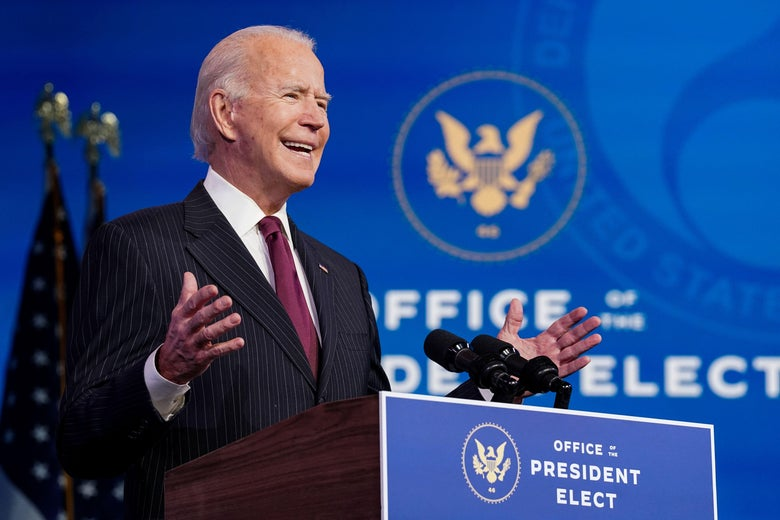 Biden speaks and gestures at a podium marked Office of the President Elect