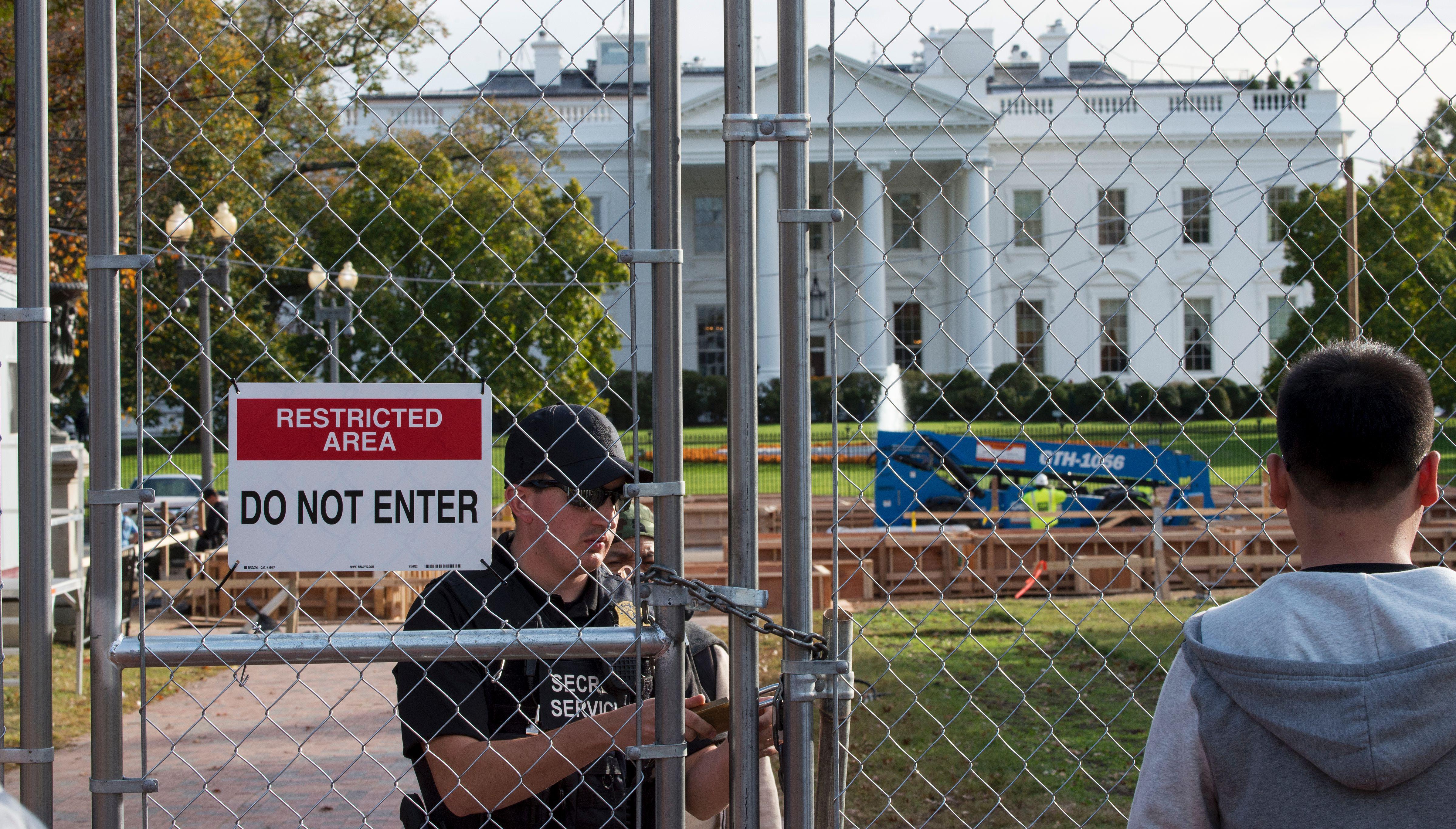 A member of the US Secret Service Uniformed Division locks a construction gate in the middle of Lafayette Square Park,near the White House as construction has started on the Presidential reviewing stand, November 8, 2016, in Washington, DC.