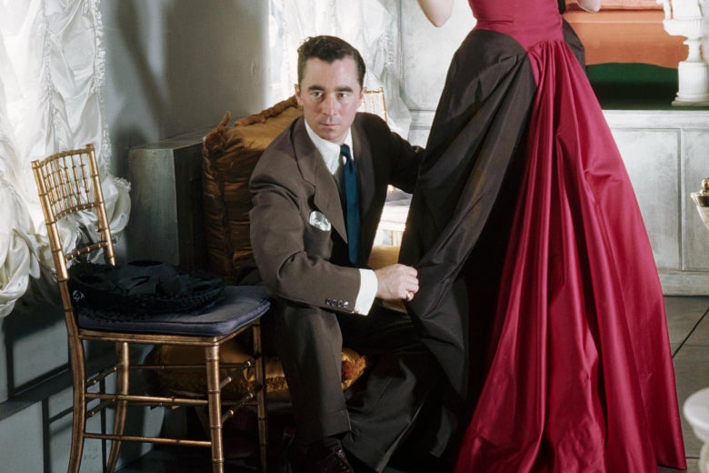 Charles James adjusts the drape on a woman's gown.
