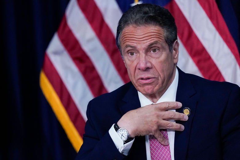 Andrew Cuomo sitting in front of a U.S. flag