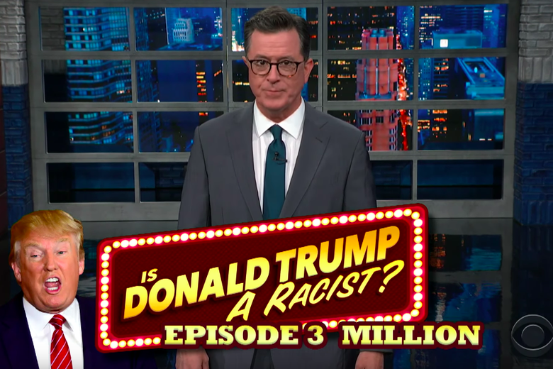 Stephen Colbert stands in front of a graphic reading Is Donald Trump a Racist? Episode 3 Million.