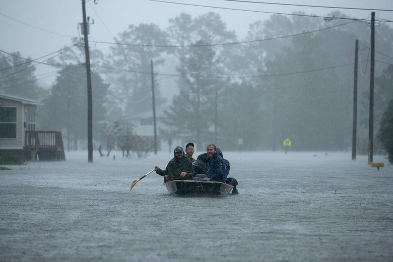 Volunteers rescue residents in a row boat in a flooded area.