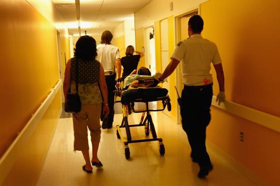 Paramedics and parents walk in an injured child into the emergency room on September 14, 2009 at the non-profit Children's Hospital in Aurora, Colorado. Although a proposed 'government option' in health care reform has stirred controversy nationally, hospital administrators say that almost half the children they admit are already covered by a government plan, mostly Medicaid.
