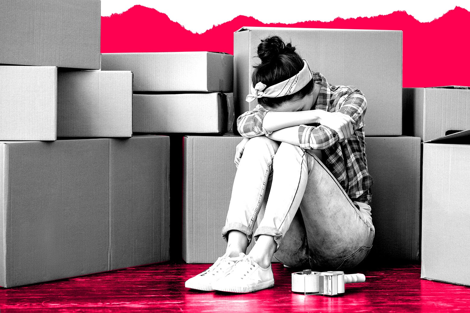 A woman looking distressed amongst many moving boxes.