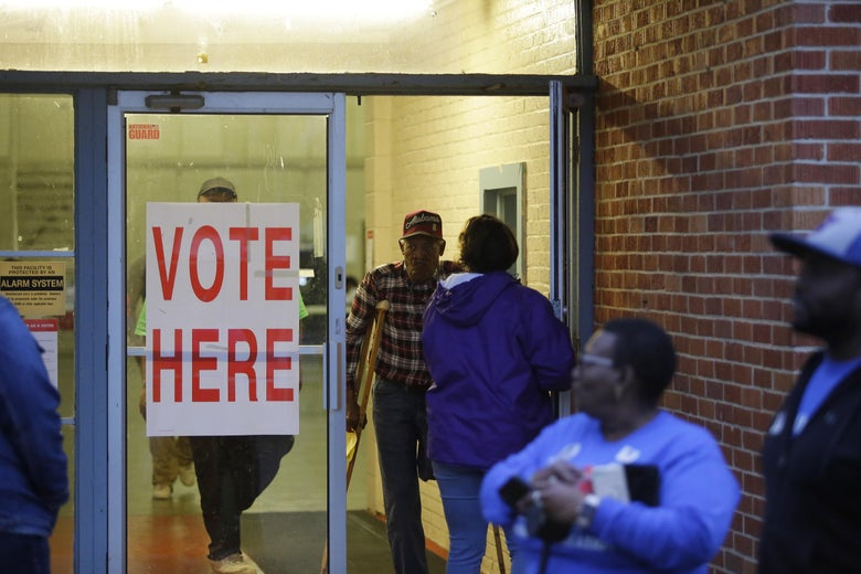 Alabama residents wait in line outside a polling station to cast a ballot.