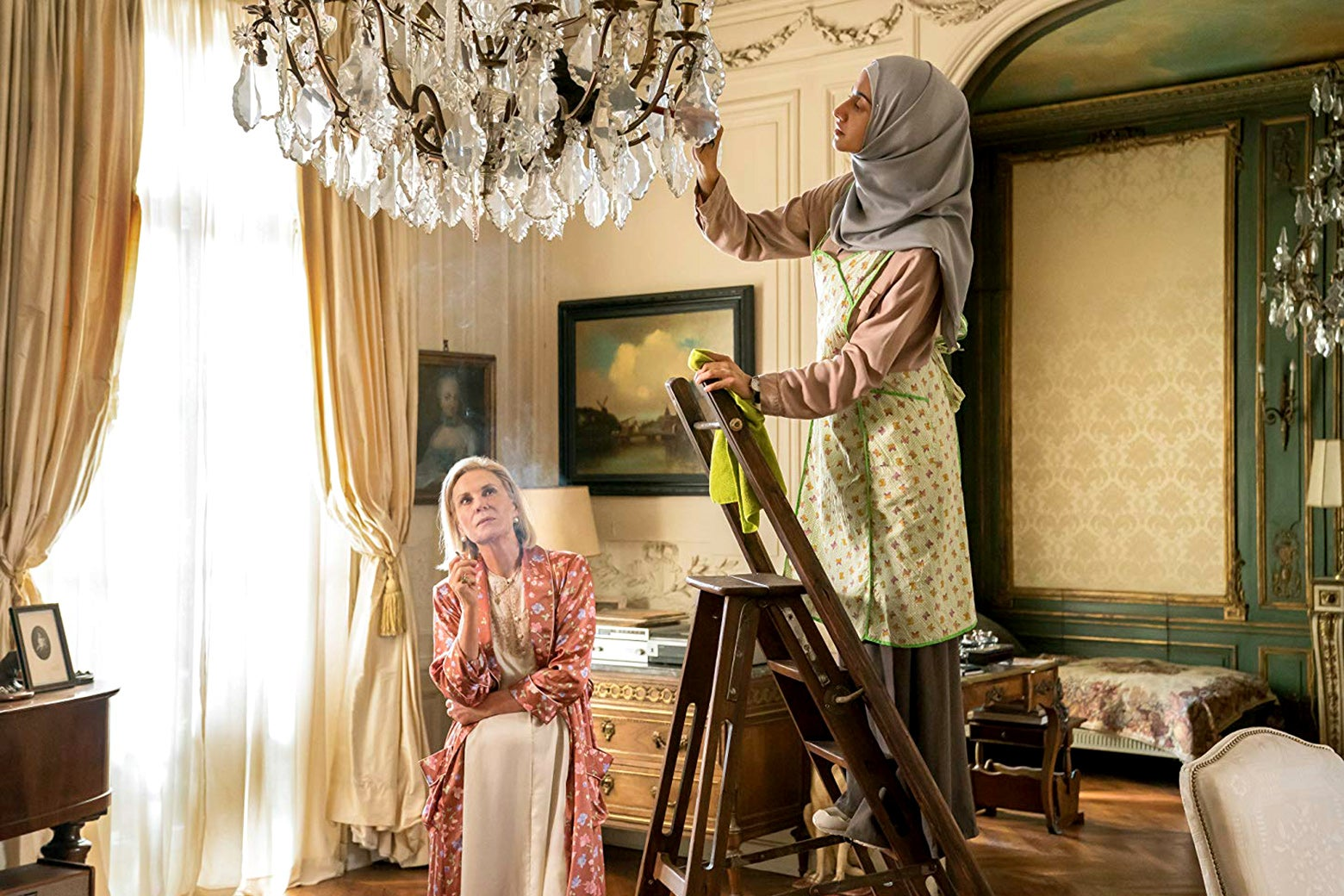 In a scene from The Romanoffs, an elderly woman sits in a richly decorated room and looks on as a younger woman in a hijab stands on a ladder, cleaning the chandelier.