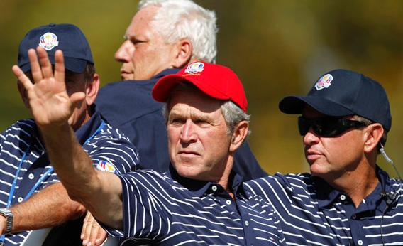Former U.S. President George W. Bush (L) sits in a golf cart with U.S. captain Davis Love III during the afternoon four-ball round at the 39th Ryder Cup.