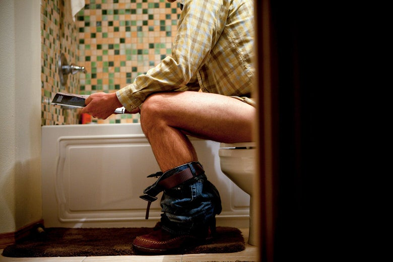 A man is seen from the side in his bathroom, pants down, sitting on a toilet, reading a magazine