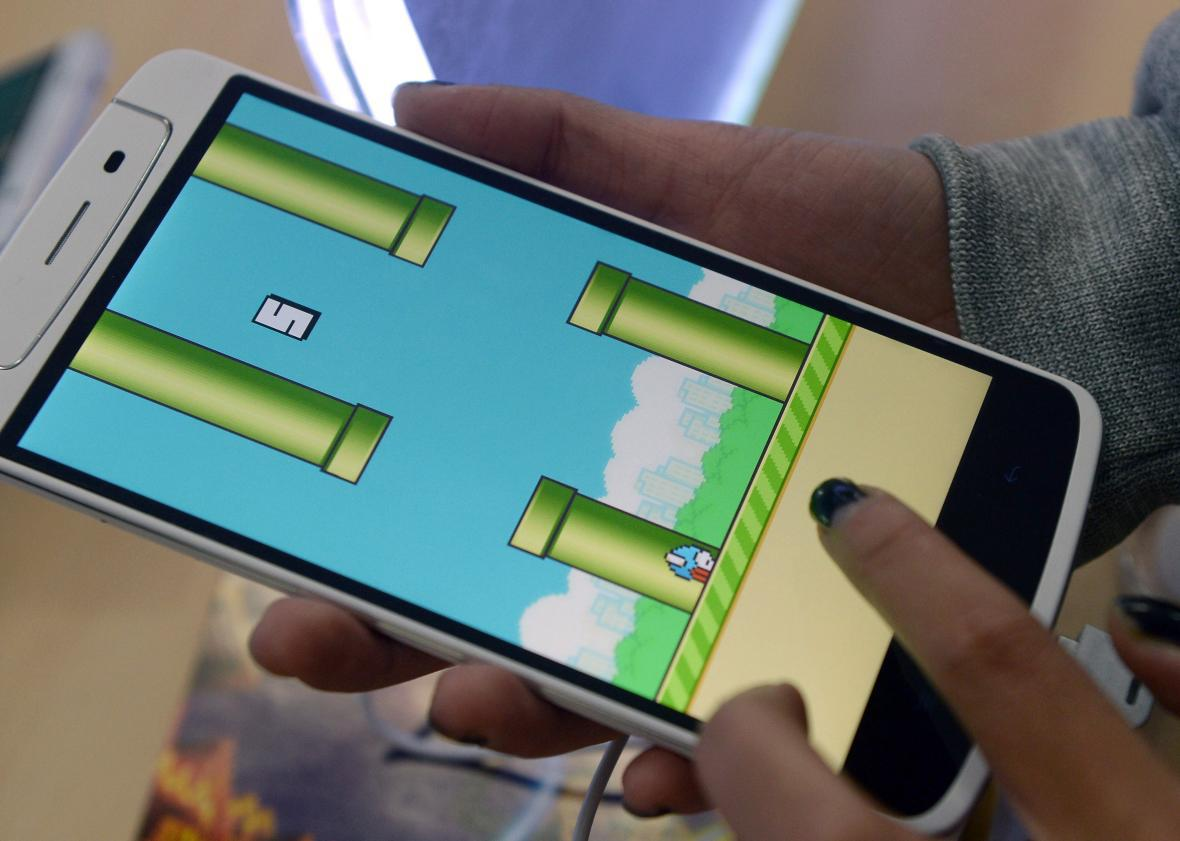 An employee plays the game Flappy Bird at a smartphone store in Hanoi on February 10, 2014.