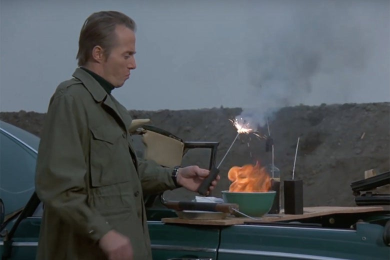 A man in a trench coat holds a cartoonish dynamite prop. He is lighting the fuse from flames that rise from a green mixing bowl, which is next to several other bombs.