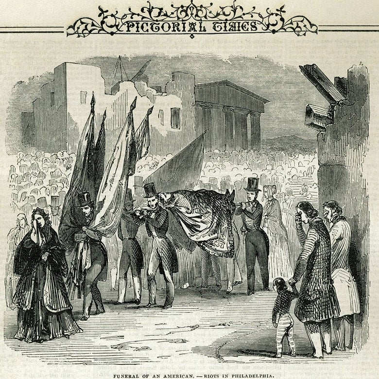 Image of a crowd with several members carrying a body.
