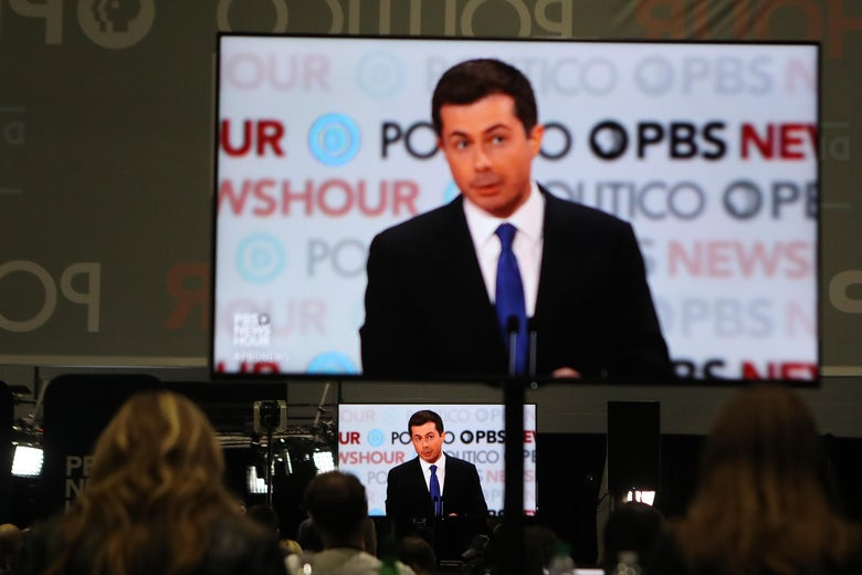 Journalists, seen from behind, sit watching a large screen above a small screen, both showing the same image of South Bend, Indiana Mayor Pete Buttigieg against the debate backdrop covered with the logos of the sponsoring news organizations. (Photo by Mario Tama/Getty Images)