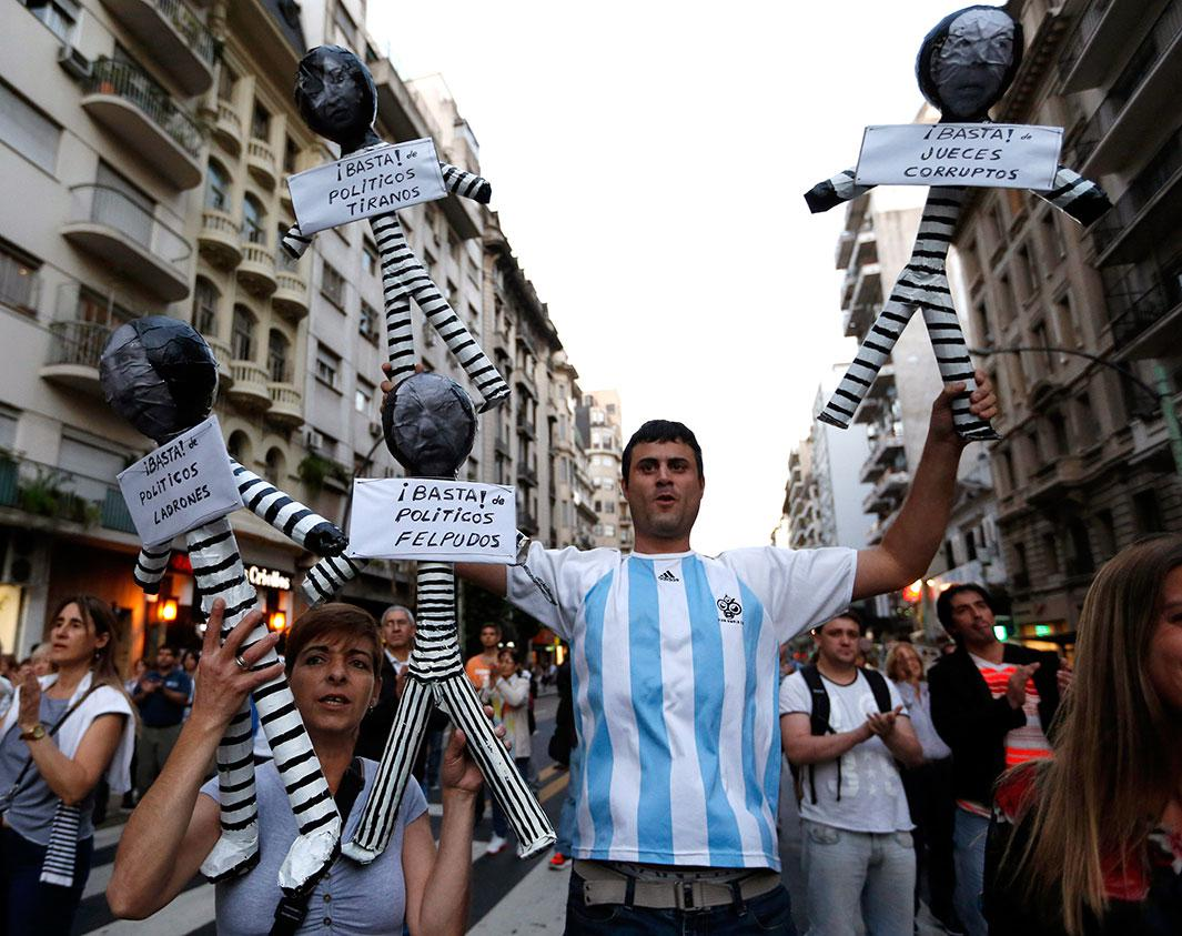 "Protesters hold effigies representing judges and politicians dressed as inmates during an anti-government rally in Buenos Aires on Nov. 13, 2014. Diverse organizations rallied against inflation, corruption, and high crime rates in widespread demonstrations organized via social media networks. The signs under the effigies read: ""Enough thieve politicians,"" ""Enough servile politicians,"" ""Enough dictator politicians,"" and ""Enough corrupt judges"""