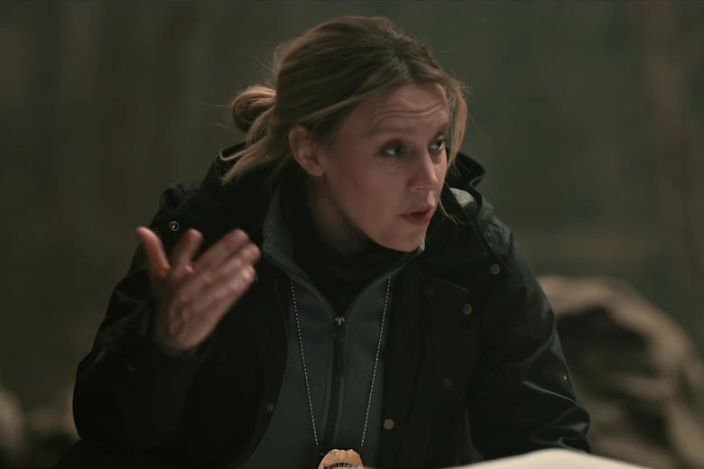Kate McKinnon, dressed like a grizzled Pennsylvania detective, kneeling in the woods over a body covered in plastic.