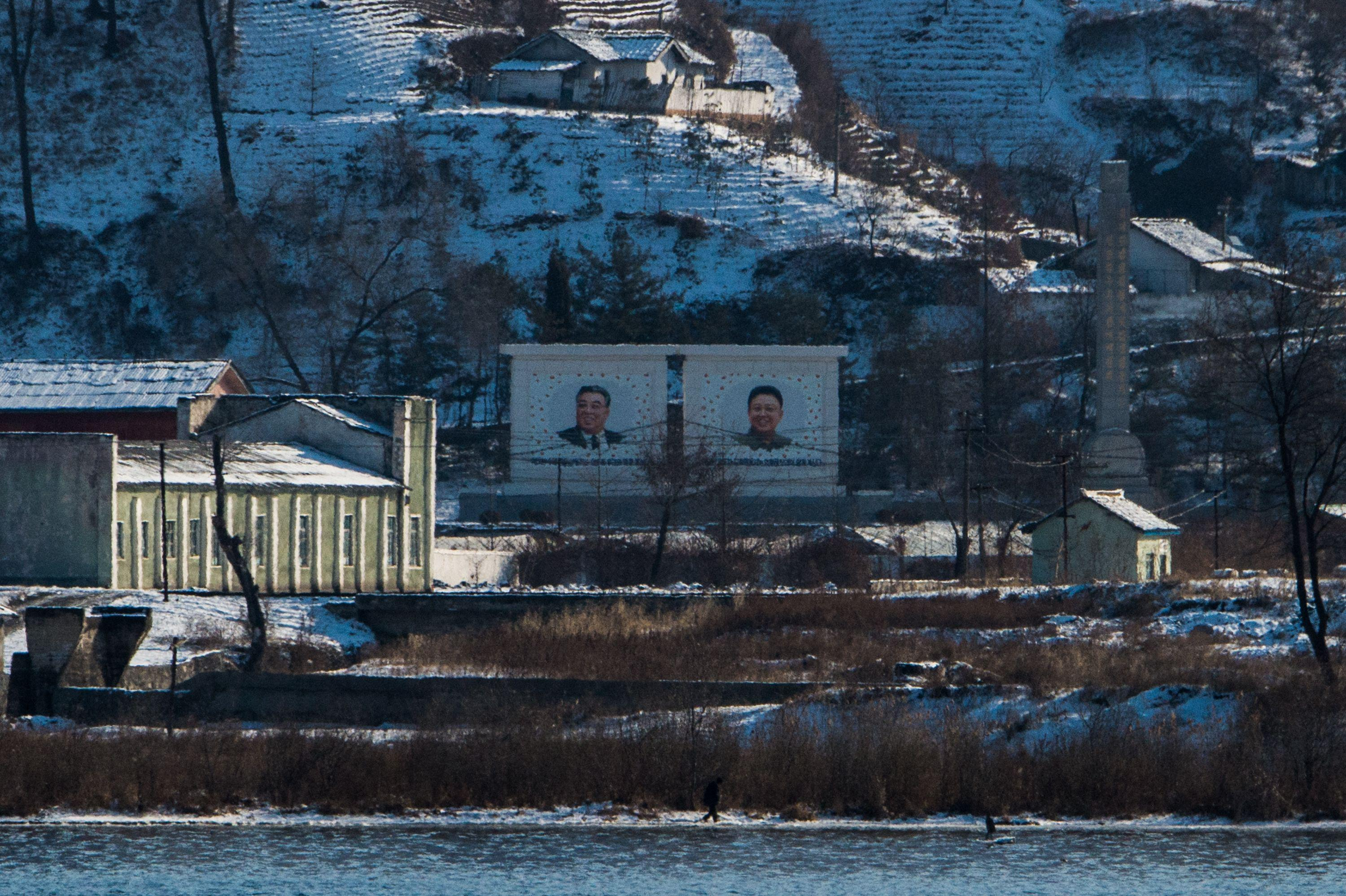 The portraits of Kim Il-Sung, left, and Kim Jong-Il in North Korea, as seen from Dandong, China, on Jan. 10.
