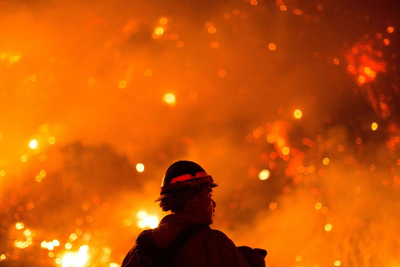 A firefighter looks at a wildfire.
