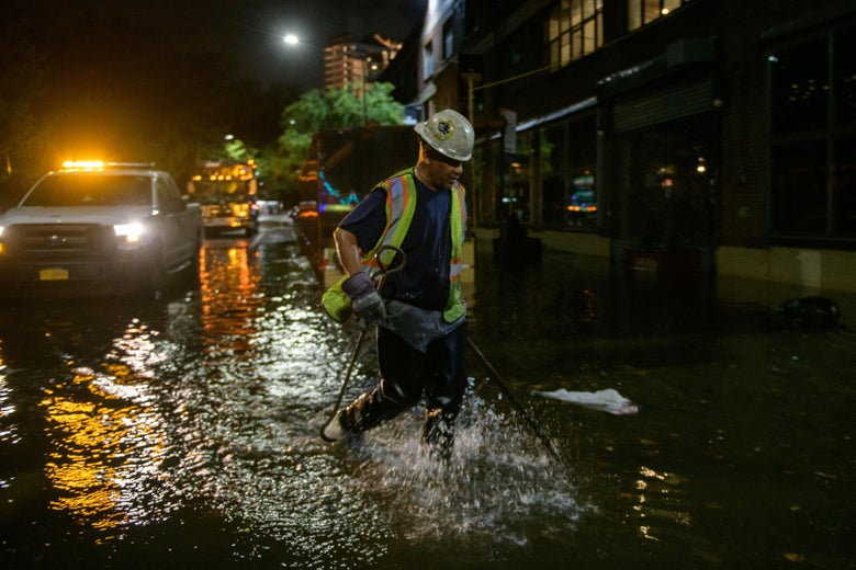 A worker unblocks drains on a street affected by floodwater in Brooklyn, New York early on September 2, 2021, as flash flooding and record-breaking rainfall brought by the remnants of Storm Ida swept through the area.