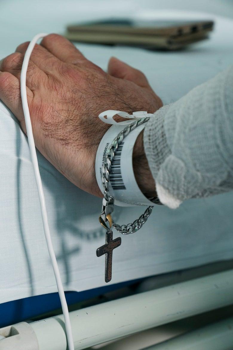 A man wearing a crucifix bracelet grasps the rail of of a hospital bed.