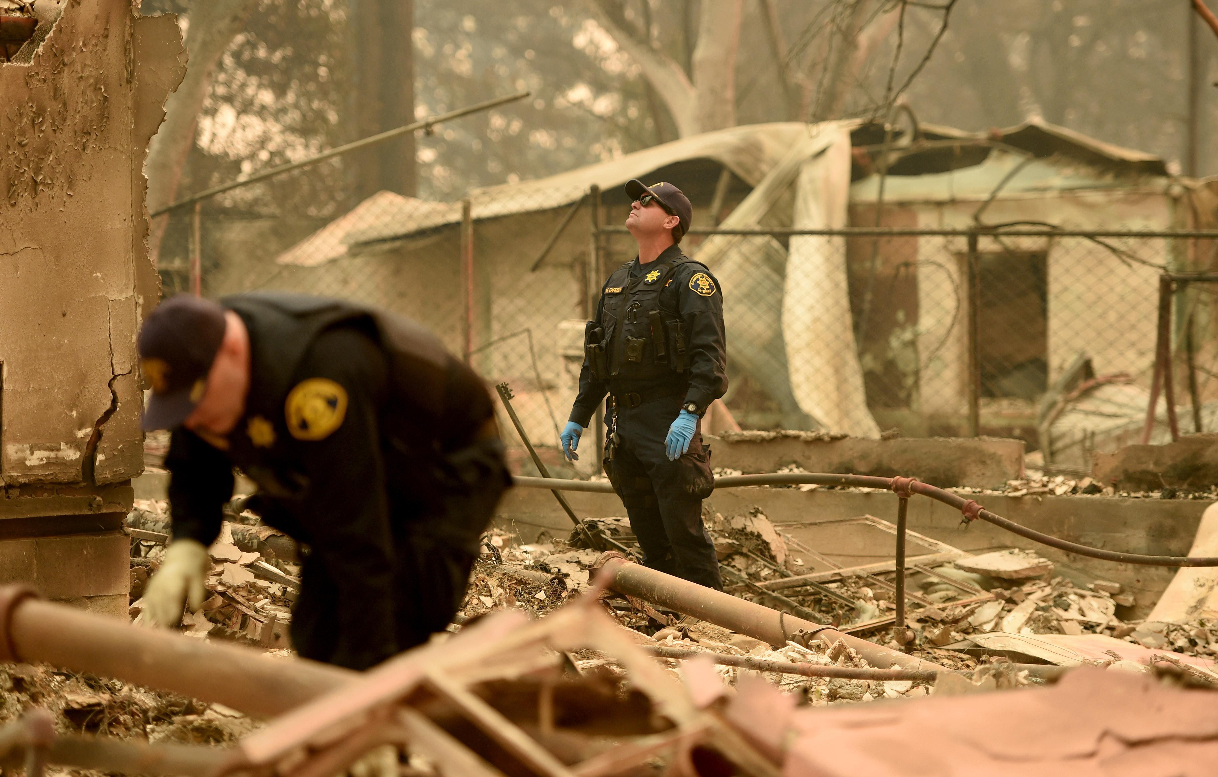 In the burned wreckage of a home, two officers wearing gloves look through the rubble. A layer of ash coats everything.