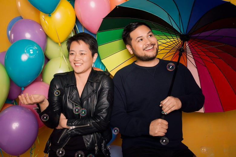 Kathy Tu and Tobin Low, with balloons of many colors in the background. Low holds a rainbow umbrella.