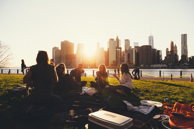 A group of people sit in a park by a river as the sun sets over a city skyline.