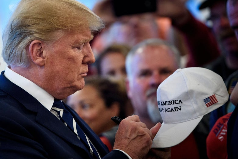 President Donald Trump signs a hat while meeting with supporters during a Bikers for Trump event at the Trump National Golf Club August 11, 2018 in Bedminster, New Jersey.