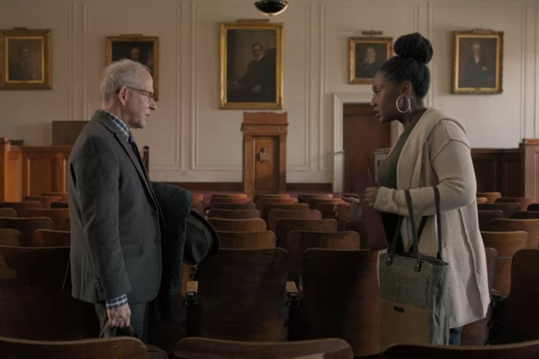 Elliot and Yaz stand in an old-looking college classroom with paintings in the front and many rows of wooden chairs.