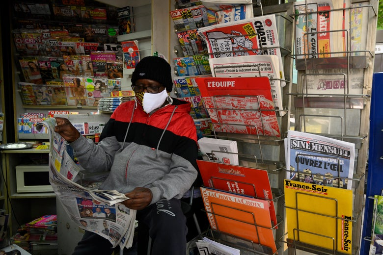A man reading the local paper at a newsstand in France.