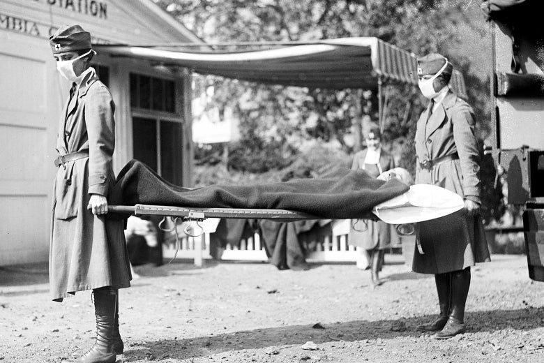 Two Red Cross workers carry a stretcher in a black-and-white photo.