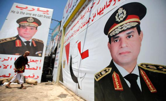 Salah Abdel Moneim, 40, an Anti-Mursi supporter of Egypt's army, walks in front of his shop, plastered with huge posters of Egypt's army chief General Abdel Fattah al-Sisi.