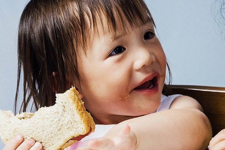 Toddler eating a peanut butter sandwich.