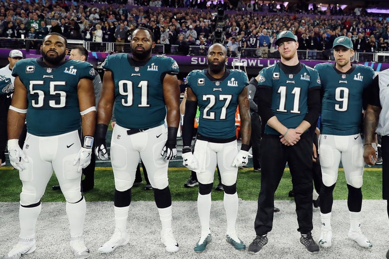 Five Eagles players stand on the sideline facing toward the camera.