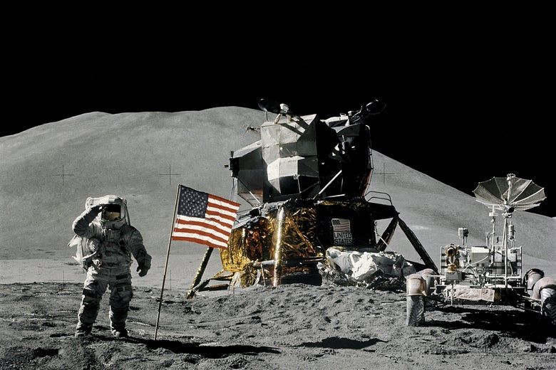 An astronaut on the moon salutes the camera while standing by an American flag and the lunar lander and rover.