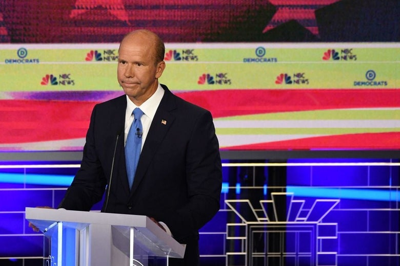 Delaney stands at a lectern with a downcast look.
