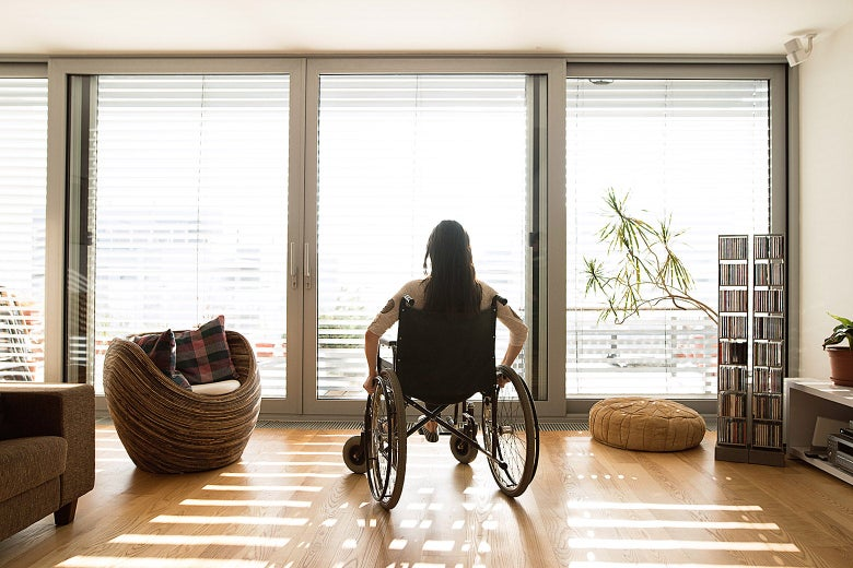 A woman in a wheelchair looking at sliding glass doors with the blinds partly open in her home.