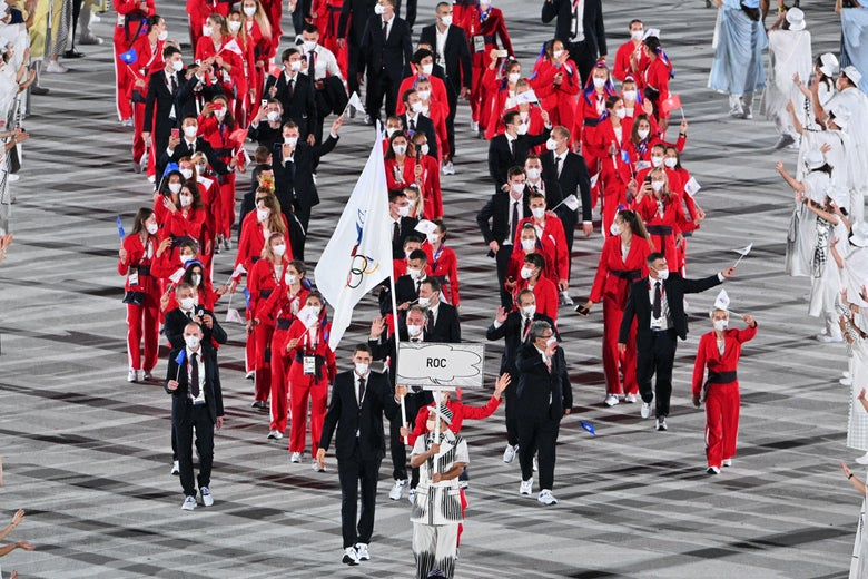 A large group of Russian athletes wearing red and black march in the Olympic stadium