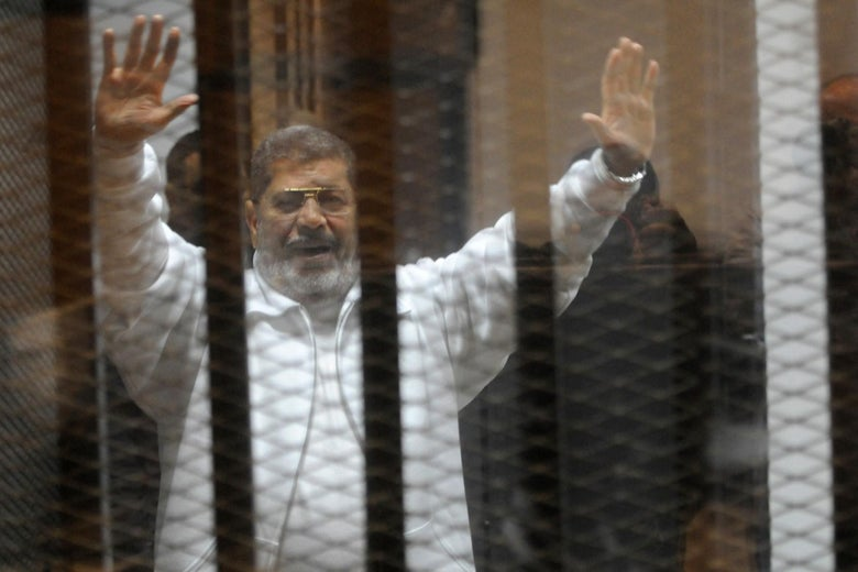 Mohamed Morsi waves from inside a cage in court