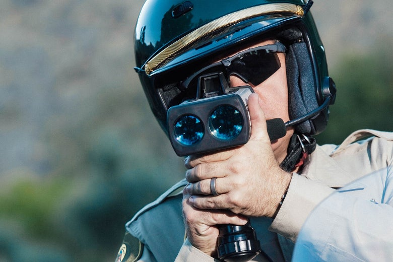 A law enforcement officer looks into a camera or radar device.