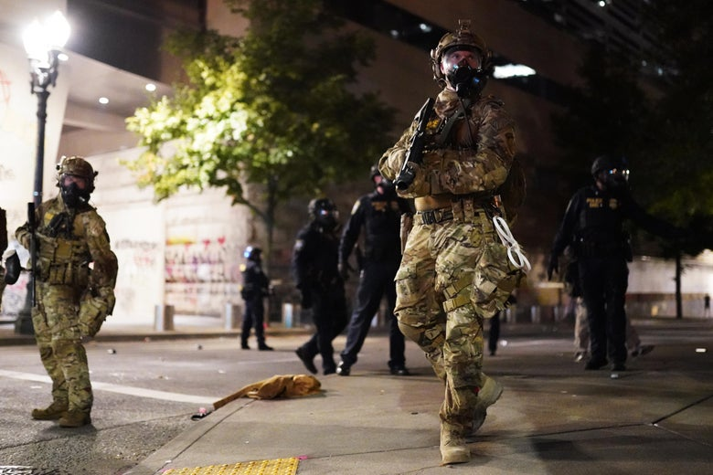 A paramilitary unit in camouflage gear holding some kind of rifle.