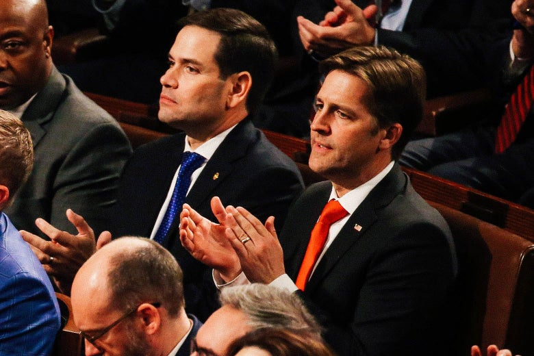 Sasse claps while seated on a bench next to Florida Sen. Marco Rubio.